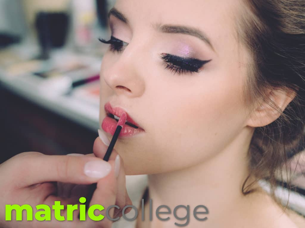 A model applying makeup on her face.