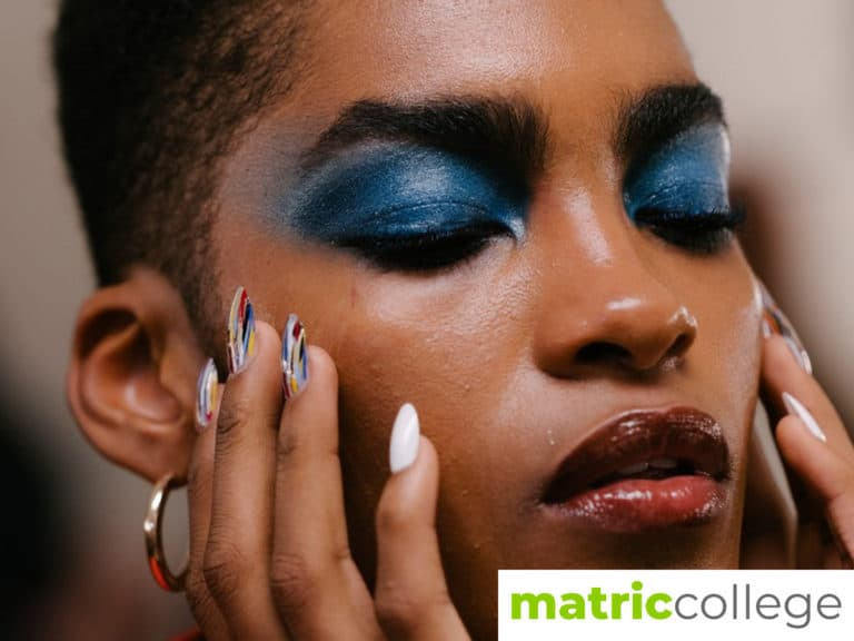 A black model adoring her face with layers of make up, her manicured hands cupping her face. Her lips are a dark shade of red and the eyes are layered in a shade of blue mascara.